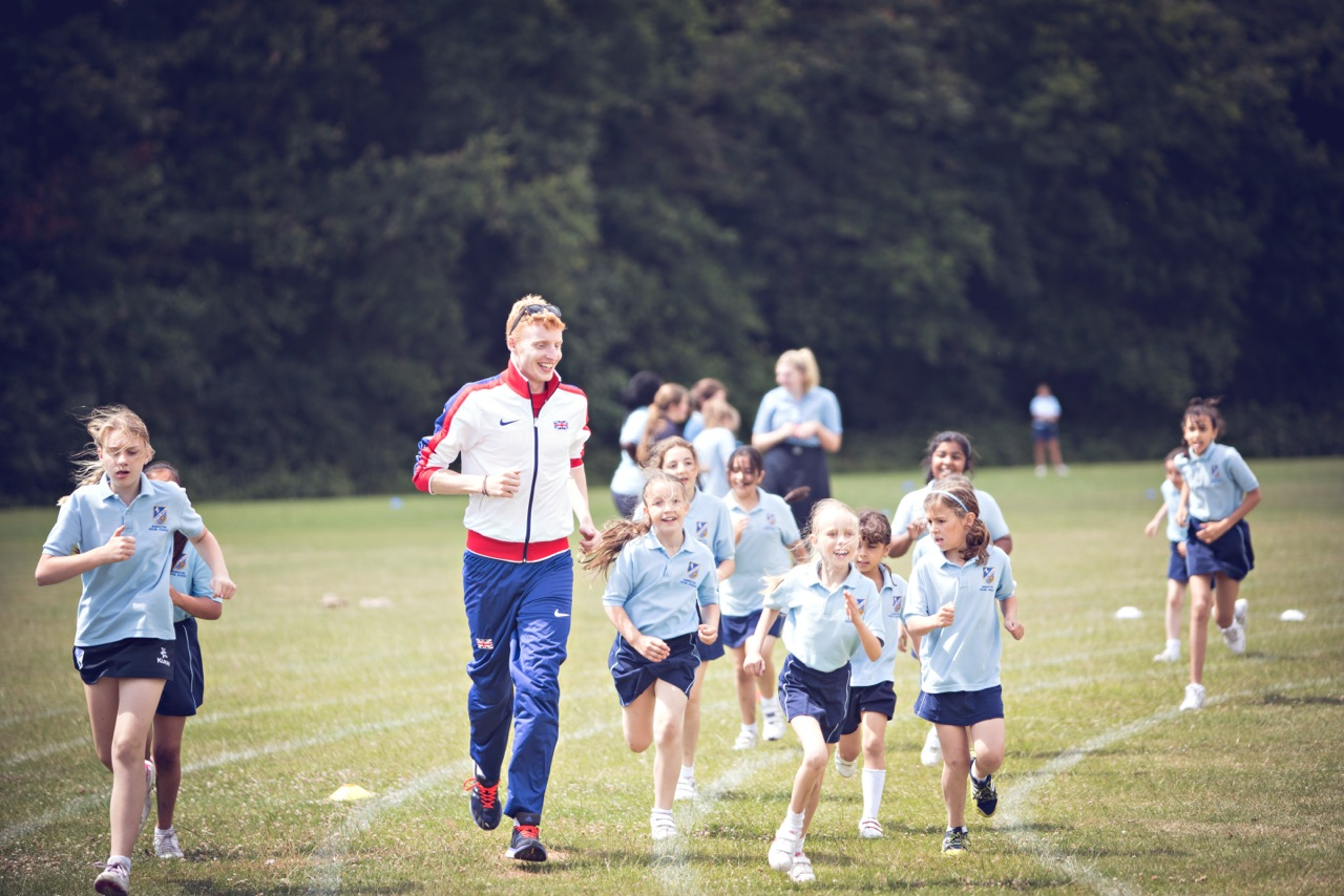 Phil Hurst running a lap with the pupils